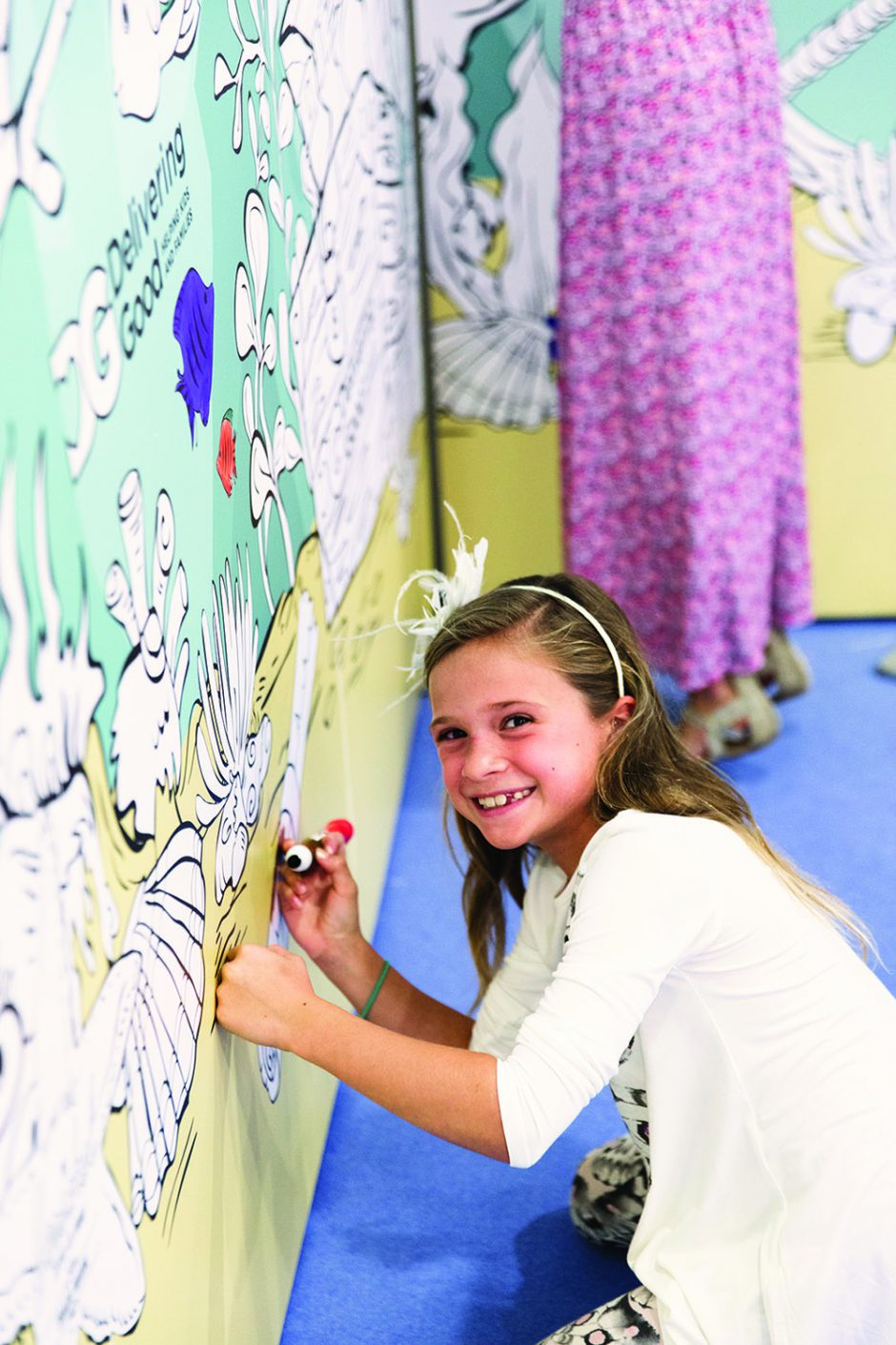 Kids enjoy an oversized coloring book wall.