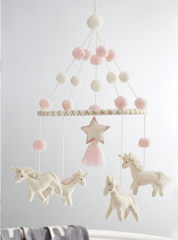 Decorate the crib with this hand-crafted mobile, including four boiled-wool unicorns with yarn pom-pom accents  and a looped cotton cord for easy hanging.