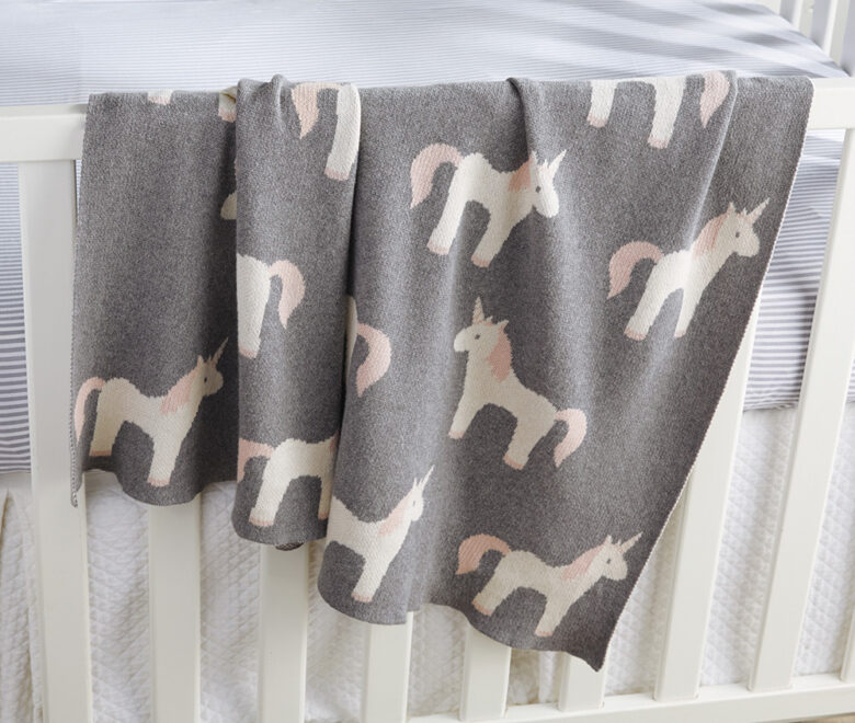Add a pop of pattern to the crib or rocking chair with this cotton  blanket of knit-in unicorn motifs.