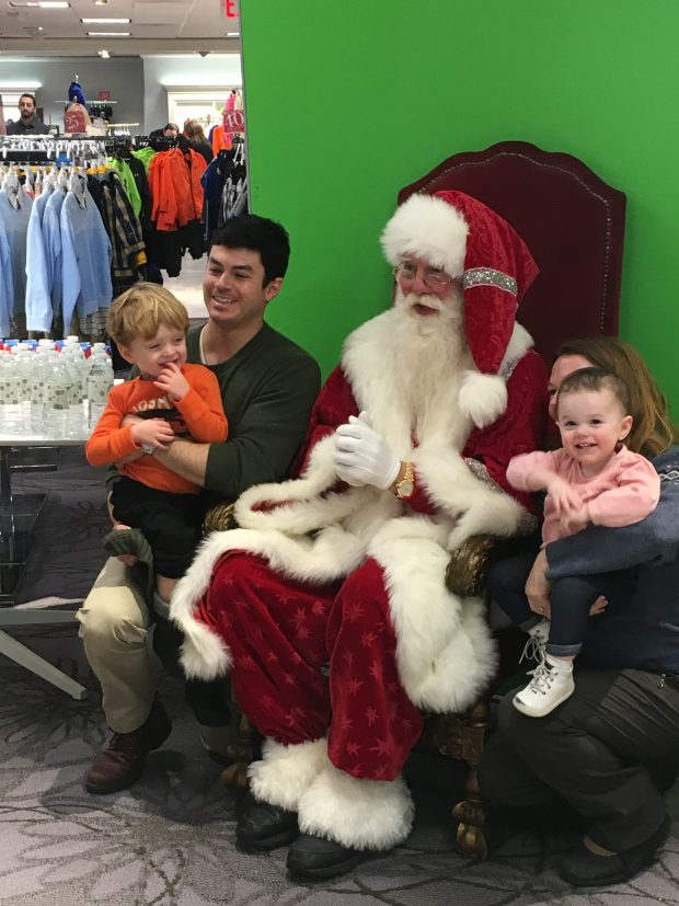 A family poses for a complimentary photo with Santa.