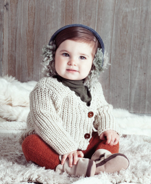 Ava wears Tia Cibani Kids green turtleneck and  shaggy earmuffs, Oeuf cardigan, leggings by Oh Baby and Robeez booties.