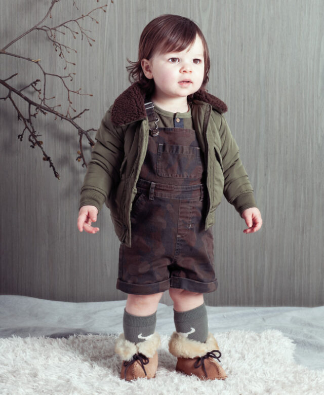 Niall wears Hudson Kids bomber jacket and Henley top, Blu & Blue camo shortalls, Booso socks and Bearpaw boots.
