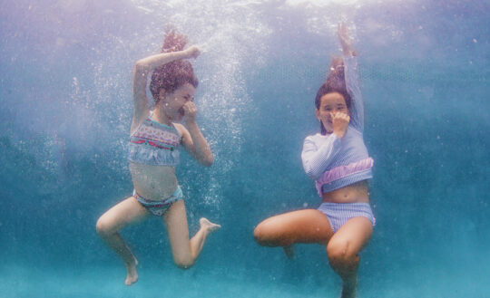 From left: Maddie wears Floatimini ruffle bikini; Marissa wears RuffleButts long-sleeved swim top and bottom.