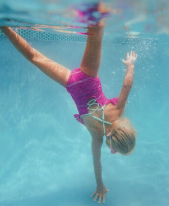 Aurora wears Coral & Reef Beachwear one-piece.