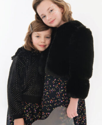 (from left to right): Layla wears Appaman black faux fur hooded pullover with black star print skirt by Molo; Peyton wears Imoga black faux fur jacket with Molo star print skirt.