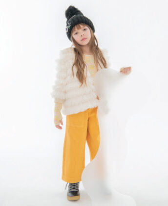 Layla wears Widgeon faux fur fringe jacket, striped shirt and yellow jeans by Molo, Young Soles black shearling lined boots and  hat by Lola + the Boys.