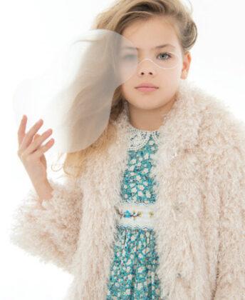 Peyton wears Lola + the Boys tie-dye faux fur coat and sequin shift dress.