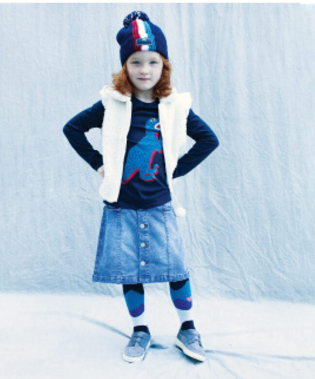 Ariana wears Mud Pie vest, Catimini tights, Paul Smith Junior hat and dinosaur shirt, Molo denim skirt, and her own shoes.