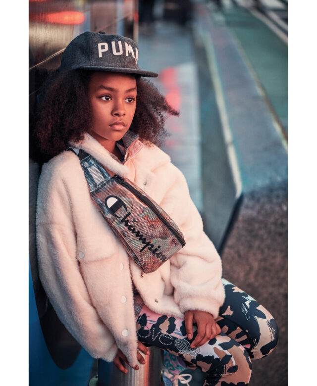 Jaelise wears Puma cap, Tractr pink coat, Bella Dahl plaid top, Big Love leggings and Champion fanny pack.
