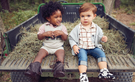 Carter wears Boboli polo, Mud Pie one-piece and soft-soled boots  by Nomandino; John wears sweater, shirt and jeans by Aimama with Twisted X cow print shoes.