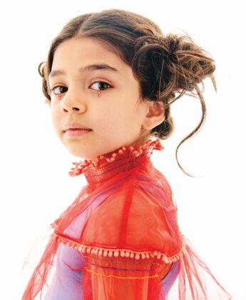 Samsara wears Pink Chicken dress underneath coral blouse by Tia Cibani.